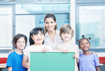 Happy beautiful female teacher with her multiethnic schoolchildr