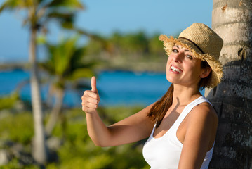 Happy woman on tropical vacation with thumbs up