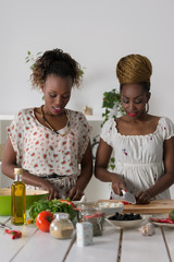 Two african women cooking salad