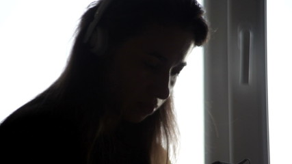 Silhouette of a girl in headphones. Listening to music near the