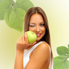 Beautiful young woman with green apple on light green