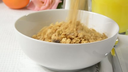 Pouring oat granola into a bowl