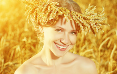 beautiful happy girl in wreath in wheat field in summer