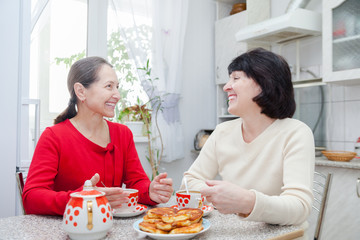mature women talking at   kitchen table