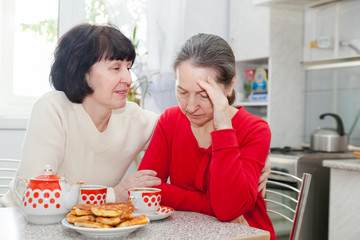 mature women talking   in   kitchen.