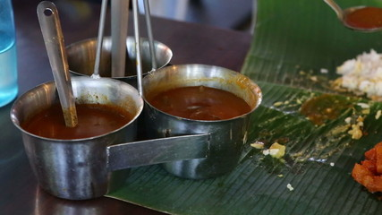 white man pours out dressings onto Indian food on banana leaf li