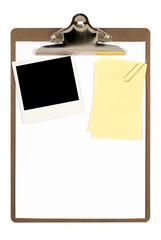 Clipboard with blank instant print picture and untidy note paper