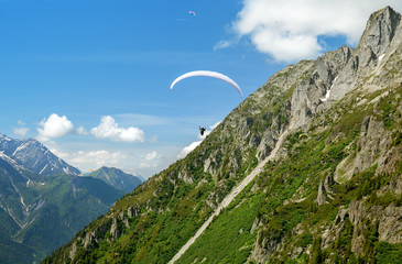 paraglider flys in the mountains in summer day