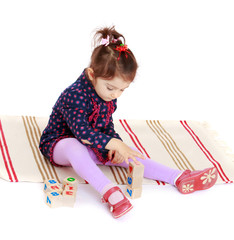 Cute little girl puts cubes sitting on the carpet.