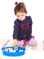 Cute little girl puts cubes sitting on the floor.