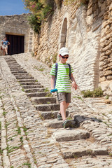 the boy is walking down stone steps