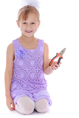 Smiling little girl holding a pliers.