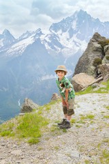 The boy with Toy dog stands on mountain path