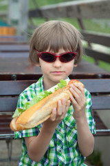 the boy in sunglasses with a great sandwich
