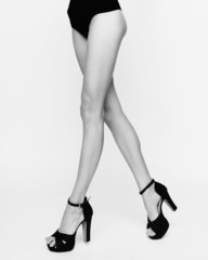 Close-up of young woman's legs in high-heeled black shoes