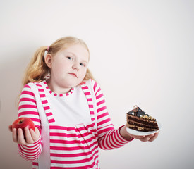 Girl choose from sweet cake and red apple