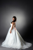 Modest bride posing in elegant dress with plume