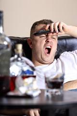 A man yawns watching TV