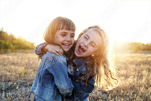 Two young girls have fun outside - 78237584