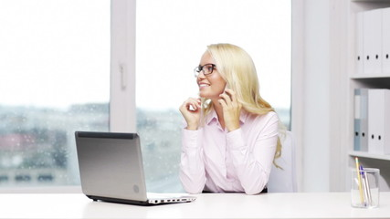 smiling businesswoman with laptop and smartphone