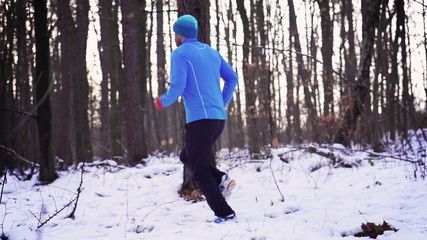 Man jogging in the forest at winter, steadycam shot, slow motion