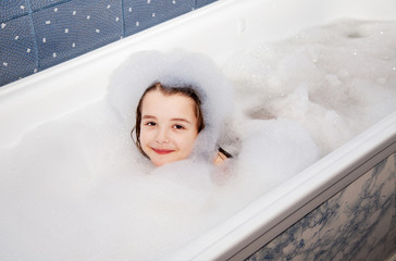 little girl lying in a bath with soap suds