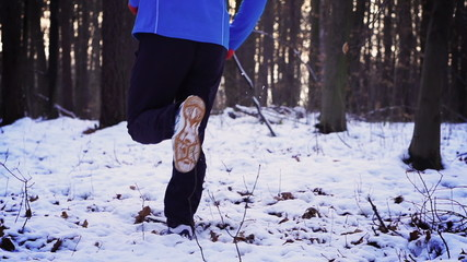 Man exercising in the snowy forest, steadycam shot, slow motion