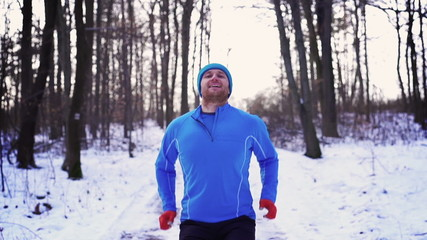 Happy man jumping in the snowy forest, steady, slow motion