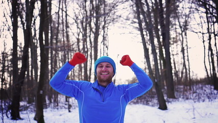 Happy man jumping in the snowy forest, steady, slow motion shot