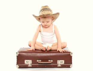 Child in a straw summer hat sitting on the suitcase
