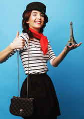 young woman holding little metal eiffel tower