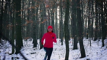 Woman running in the forest at winter, steady, slow motion