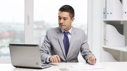 smiling businessman with laptop and papers
