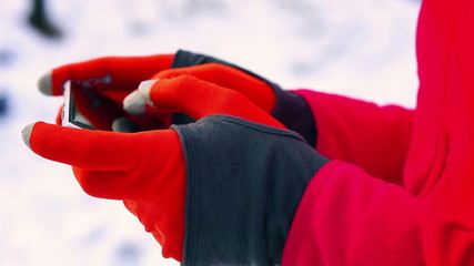 Woman typing on smartphone in gloves, closeup,steady,slow motion