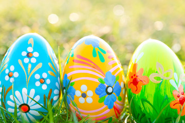 Handmade Easter eggs on grass. Spring patterns art, unique.