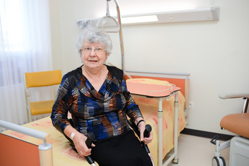 cheerful senior woman walking with crutches in hospital room