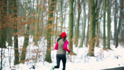 Jogger running in the forest at winter time, steady,slow motion