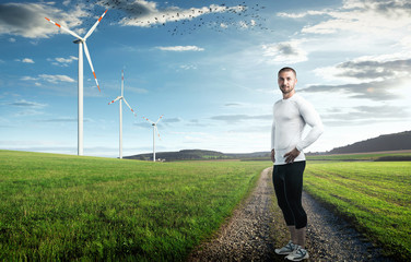 Attrakiver Läufer in schöner Landschaft mit Windrädern