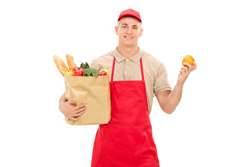 Retail worker holding an orange and a grocery bag