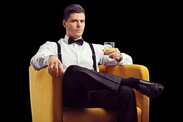 Man sitting in an armchair and drinking whiskey
