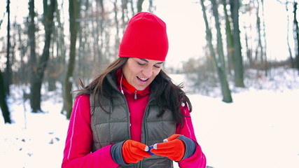 Jogger checking cellphone in the snowy park, steady, slow motion