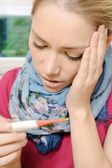 Frau mit Grippe und Erkältung misst Fieber