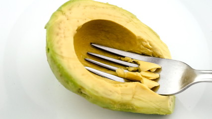 Mashing avocado into paste in slow motion with fork