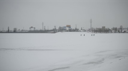 Group of people walking on frozen water storage reservoir