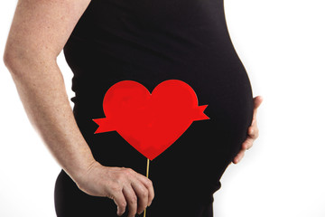 pregnant belly with heart sign