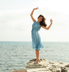 Young happy woman posing near sea