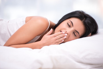 Young dark haired woman yawning in white bed