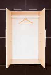 one wooden coat hanger on clothes rail in the closet. Empty