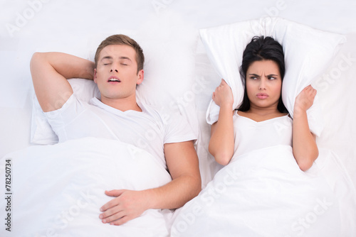 Angry woman and snoring man in bed - 78250734