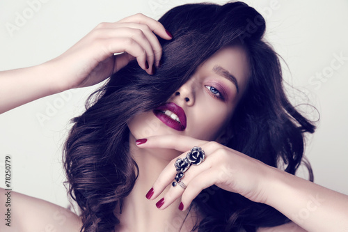 Fototapeta beautiful woman with dark hair and bright makeup with bijou